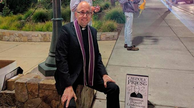 El sacerdote que ofrece confesiones y consejo afuera de un festival musical juvenil